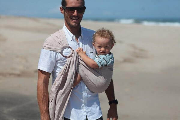 Pai com bebê em sling de argola